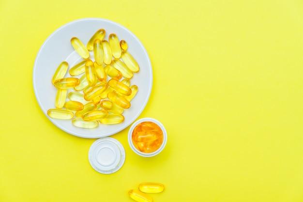 Supplément d'huile de poisson, concept médical et de santé, vue de dessus des écarts de gel mou sur le mur jaune