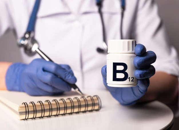 Supplément de vitamine b12 dans un pot blanc dans les mains du médecin dans des gants.