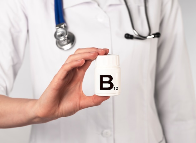 Supplément de vitamine b12 dans un pot blanc entre les mains du médecin.