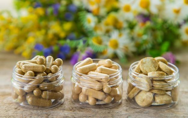 Suppléments et vitamines sur des bocaux en verre sur une table en bois avec fond de végétation floue