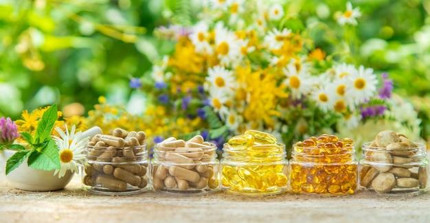 Suppléments et vitamines dans des bocaux en verre sur une table en bois avec fond de fleurs floues