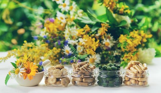 Suppléments et vitamines dans des bocaux en verre sur un tableau blanc avec fond de fleurs floues