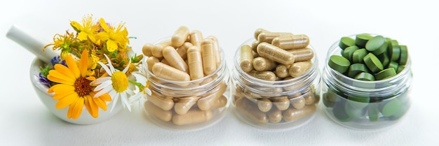 Suppléments, vitamines et herbes médicinales dans des bocaux en verre sur une table blanche