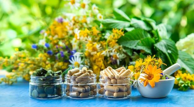 Suppléments, vitamines et herbes médicinales dans des bocaux en verre sur une table bleue avec fond de plantes floues
