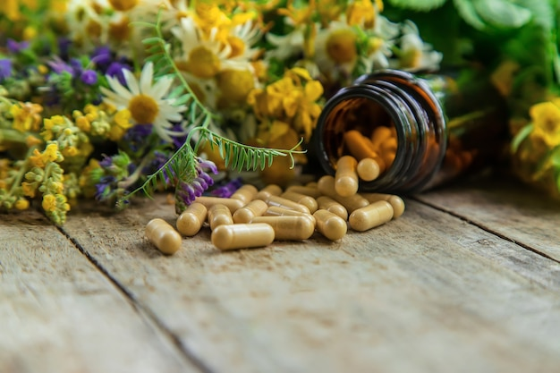 Suppléments, vitamines et herbes médicinales dans des bocaux en verre sur une table en bois