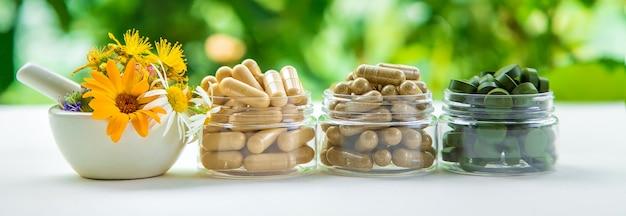 Suppléments, vitamines et herbes médicinales dans des bocaux en verre sur un tableau blanc avec fond de plantes floues