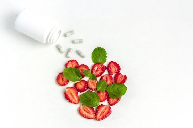 Suppléments de vitamines sous forme de capsule avec des baies fraîches de pot de médecine.
