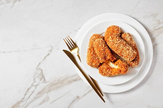 Suppli al telefono italien ou croquettes de riz farcies à la mozzarella servies sur une assiette blanche avec des couverts dorés sur fond de marbre clair, vue de dessus, espace pour copie