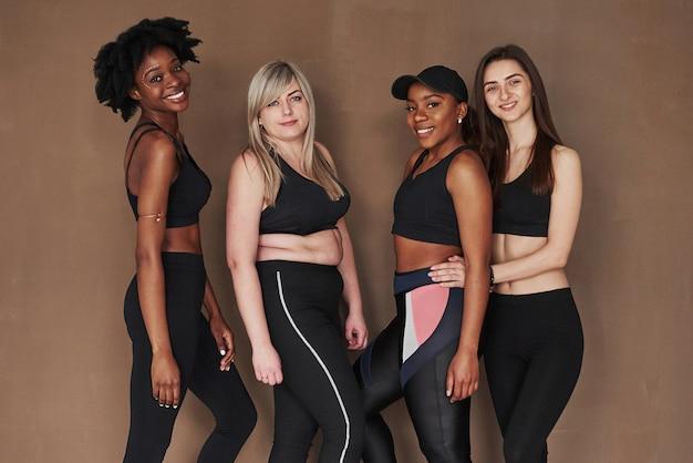 Support amical. groupe de femmes multiethniques debout contre l'espace brun