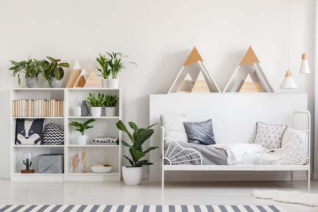 Support en bois avec des livres, des plantes fraîches et des coussins à l'intérieur d'une chambre blanche avec un tapis moelleux à côté d'un lit en métal