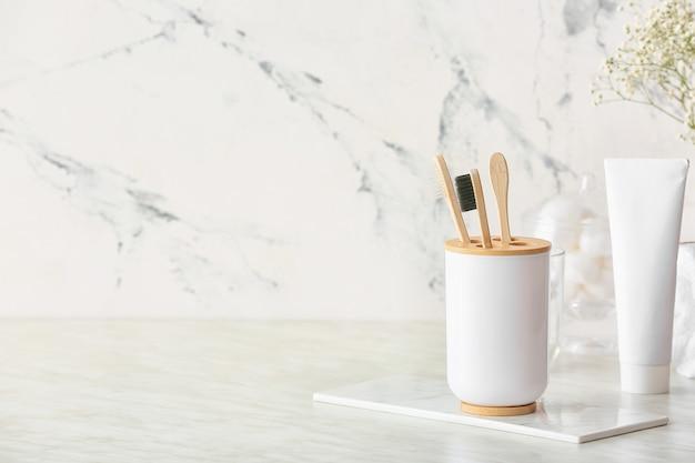 Support avec brosses à dents en bois et dentifrice sur table dans la salle de bains