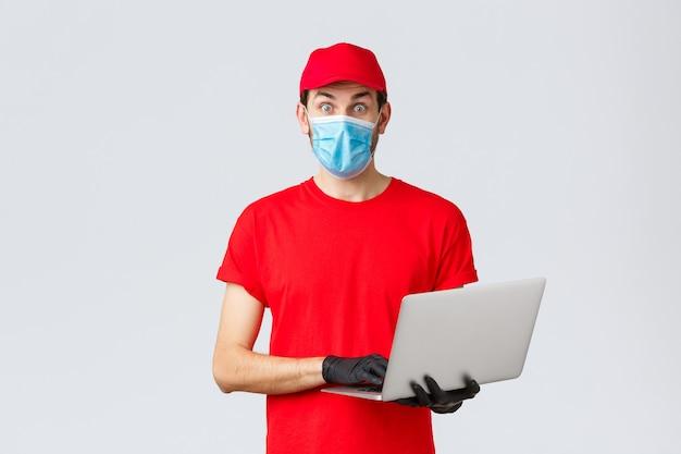 Support client, colis de livraison covid-19, concept de traitement des commandes en ligne. courrier surpris en uniforme rouge, masque facial et gants, caméra fixe, tenant un ordinateur portable, lisez des nouvelles intéressantes