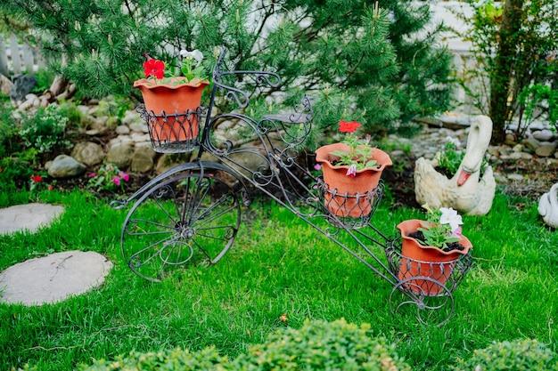Support décoratif pour fleurs en pots en forme de vélo dans le jardin. éléments de décor de conception de paysage pour les parcs et les maisons de campagne d'arrière-cour.
