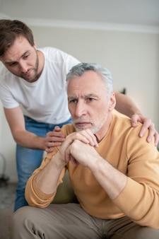 Support. homme mûr semblant triste, son fils le soutenant