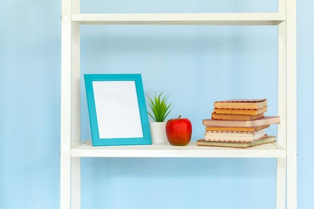 Support en métal blanc avec des livres sur fond bleu