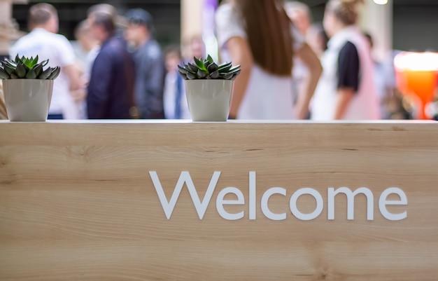 Support de réception en bois clair avec une inscription blanche bienvenue. sur une grille, des plantes dans des pots blancs. en arrière-plan des gens flous