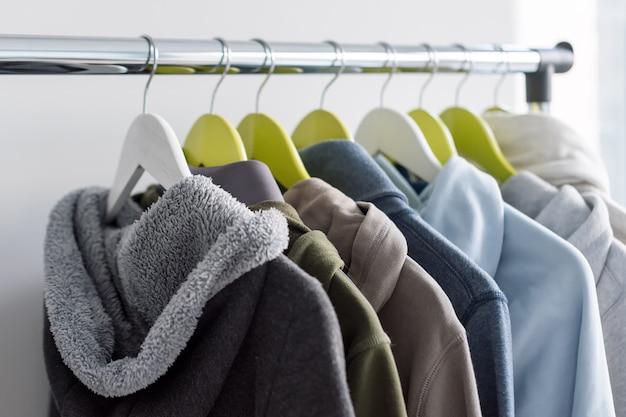 Support de suspension avec des vêtements chauds de printemps ou d'automne sur fond gris