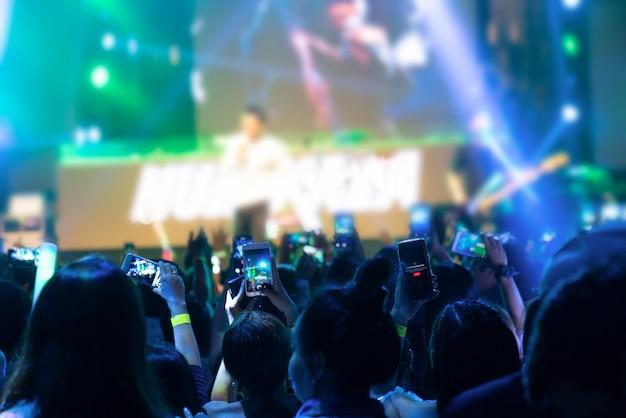 Supporters enregistrant au concert - image candide de la foule au concert de rock