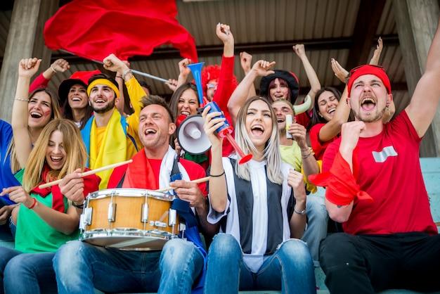 Supporters de football au stade - les fans de football s'amusent et regardent un match de football