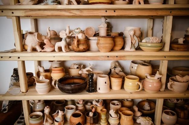 Supports en bois dans un atelier de poterie dans lequel il y a de la poterie, de nombreuses poteries différentes debout sur les étagères d'un atelier de poterie. lumière faible