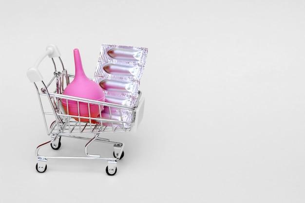 Les suppositoires médicaux dans un blister argenté et un lavement médical en caoutchouc rose sont placés dans un panier de jouets.
