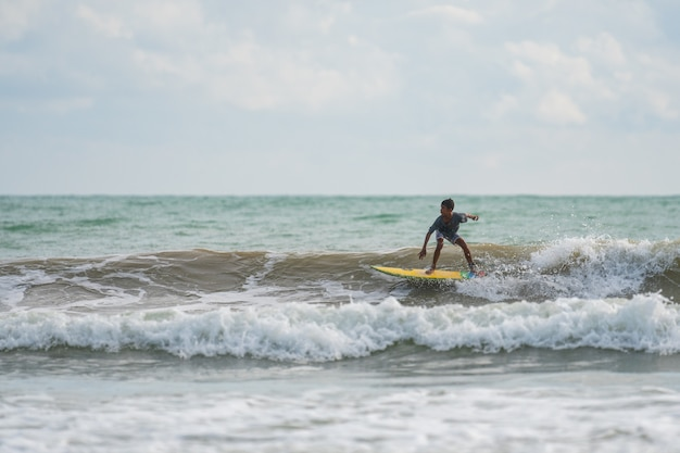 Un avec un surf dans ses mains au bord de la mer