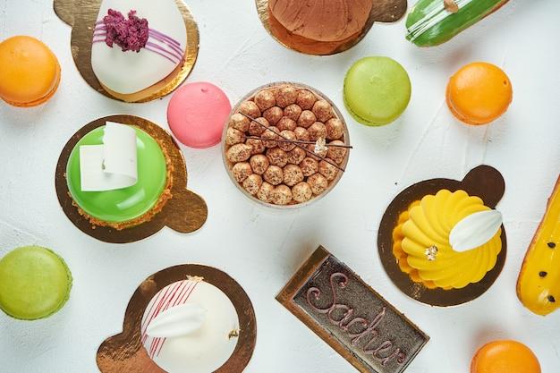 Surface appétissante avec pâtisseries, gâteaux, éclairs, macarons. vue de dessus. modèle de boulangerie alimentaire, surface blanche