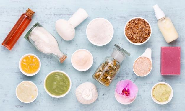 Surface d'aromathérapie du spa, pose à plat de divers produits de soins de beauté décorés de simples fleurs d'orchidées.