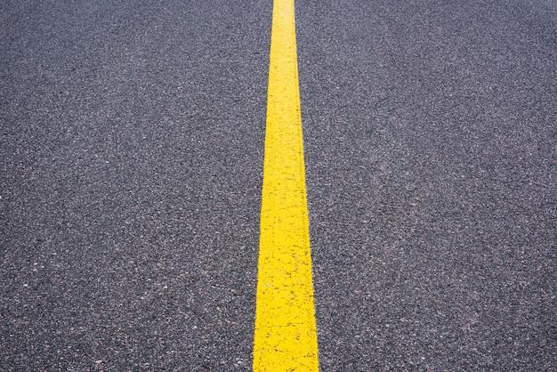 Surface asphaltée lisse avec une bande jaune.