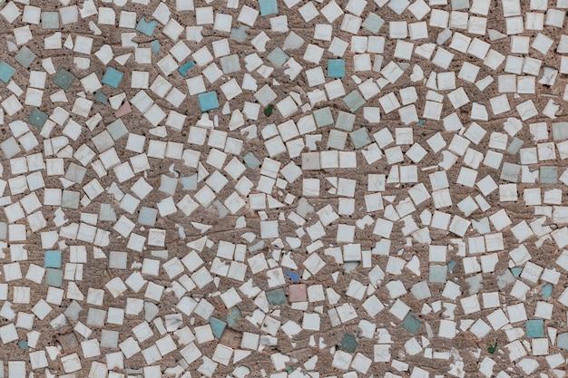 Surface en béton avec éclaboussures de nombreuses petites tuiles multicolores