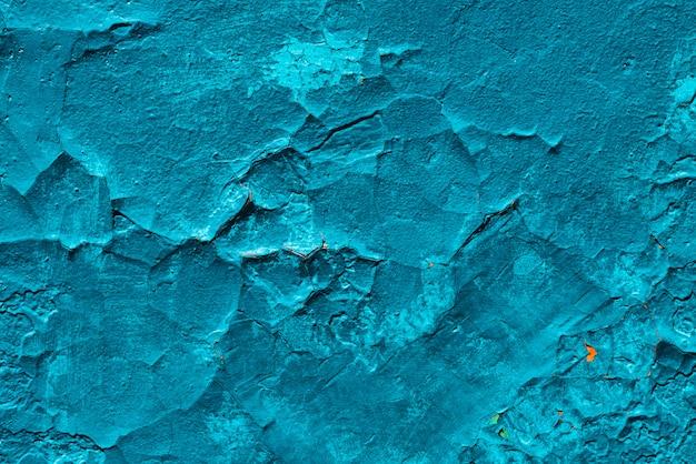 Surface de béton imparfaite. gros plan de peinture bleue fissurée.