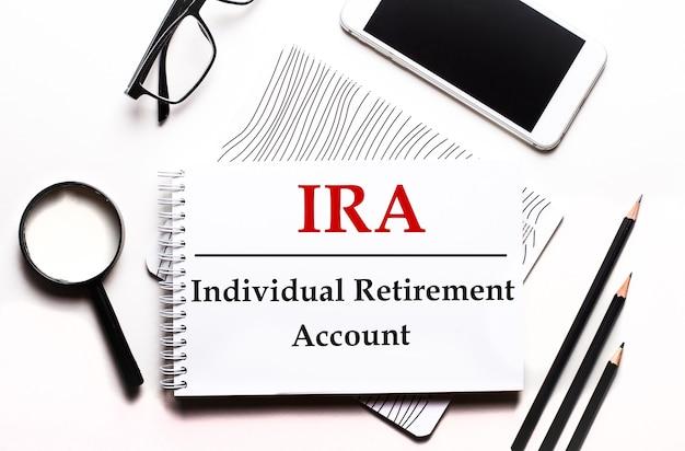 Sur une surface blanche, des lunettes, une loupe, des crayons, un smartphone et un ordinateur portable avec le texte ira individual retirement account