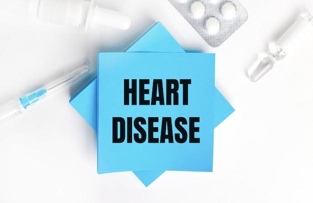 Sur une surface blanche, une seringue, une ampoule, des pilules, un flacon de médicament et des autocollants bleu clair avec l'inscription heart maladie