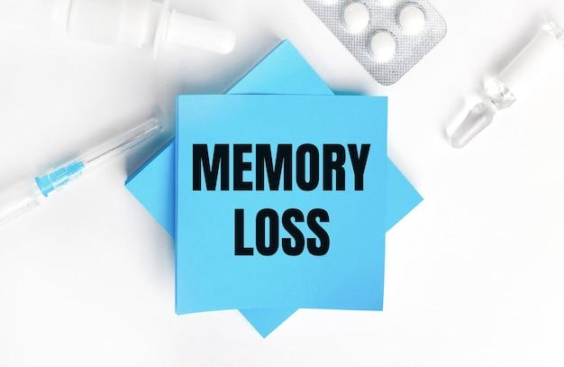 Sur une surface blanche, une seringue, une ampoule, des pilules, un flacon de médicament et des autocollants bleu clair avec l'inscription memory loss