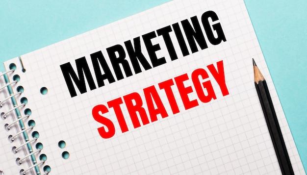 Sur une surface bleu clair, un carnet à carreaux avec les mots marketing strategy et un crayon noir
