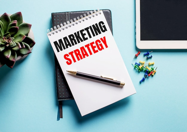 Sur une surface bleu clair, il y a une plante en pot, une tablette et un hebdomadaire avec le texte marketing strategy