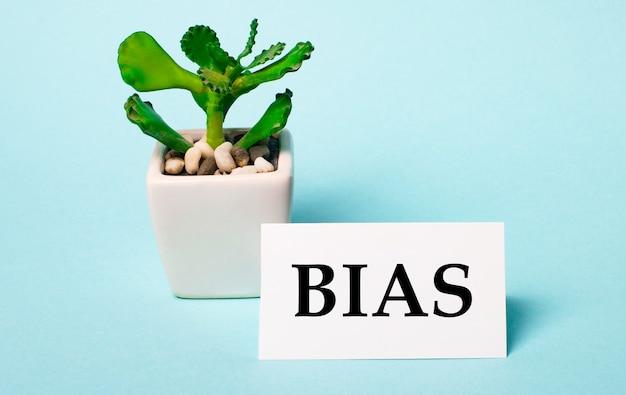 Sur une surface bleu clair une plante en pot et une carte blanche avec l'inscription bias.