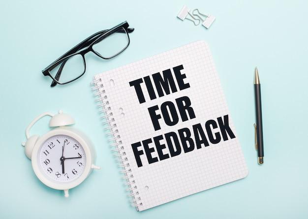 Sur une surface bleu clair se trouvent des lunettes noires et un stylo, un réveil blanc, des trombones blancs et un cahier avec les mots time for feedback. concept d'entreprise