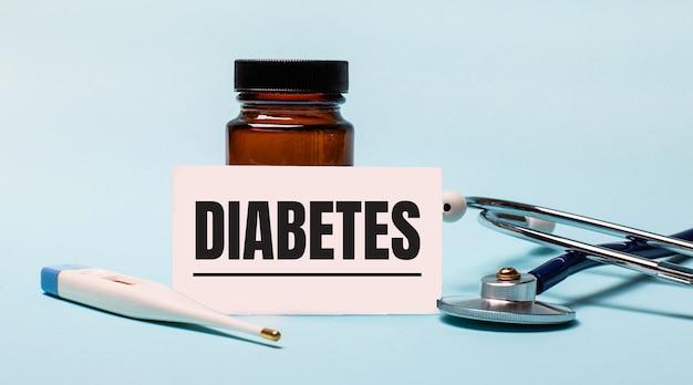 Sur une surface bleue - une bouteille pour les pilules, un stéthoscope, un thermomètre électronique et une carte avec l'inscription diabète