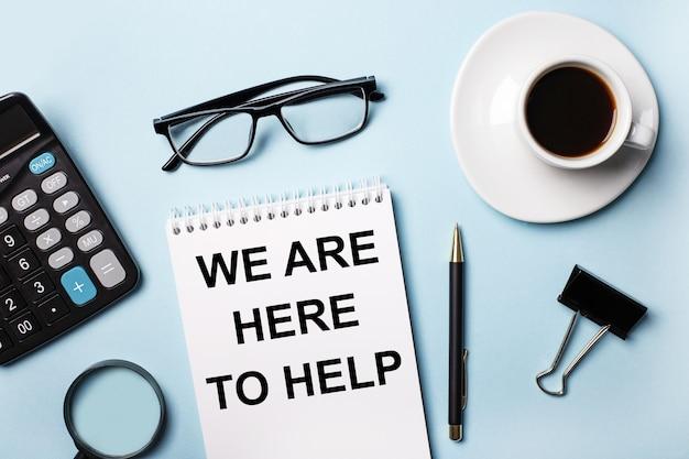 Sur une surface bleue, lunettes, calculatrice, café, loupe, stylo et cahier avec le texte nous sommes ici pour vous aider