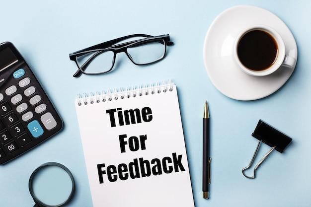 Sur une surface bleue, des lunettes, une calculatrice, du café, une loupe, un stylo et un cahier avec le texte time for feedback
