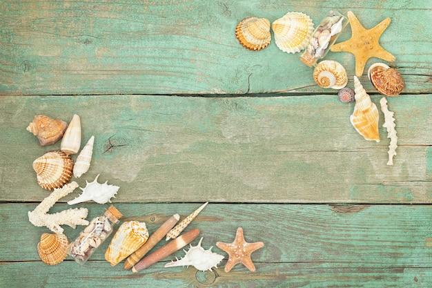 Surface bleue nautique en bois avec des coquillages, des étoiles de mer et de petites bouteilles avec des coquillages