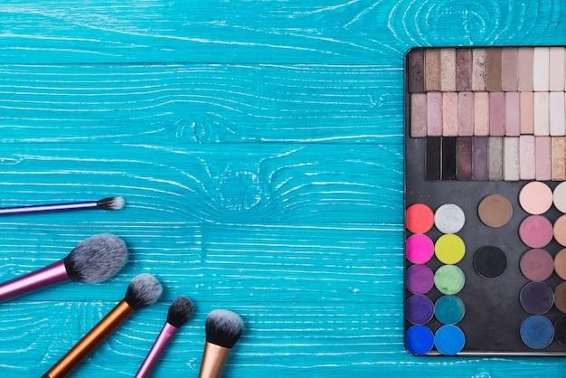Surface bleue avec des poudres et des pinceaux de maquillage