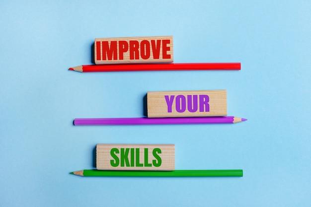 Sur une surface bleue, trois crayons de couleur, trois blocs de bois avec texte améliorez vos compétences
