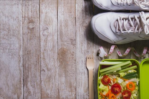 Surface en bois avec des baskets, boîte à lunch et ruban à mesurer