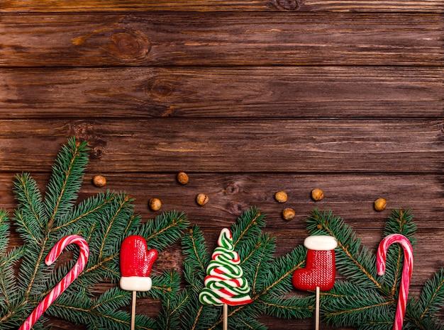 Surface en bois avec des branches de sapin et des bonbons