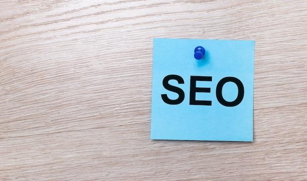 Sur une surface en bois clair, un autocollant carré bleu clair avec le texte seo search engine optimization.