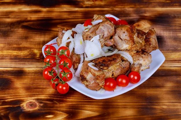 Sur la surface en bois du plateau se trouve un shish kebab, un barbecue.