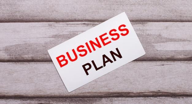 Sur une surface en bois, il y a une carte blanche avec du texte rouge plan d'affaires