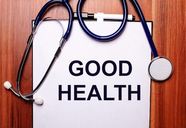 Sur une surface en bois se trouvent un stéthoscope et une feuille de papier avec l'inscription bonne santé. mise à plat. concept médical